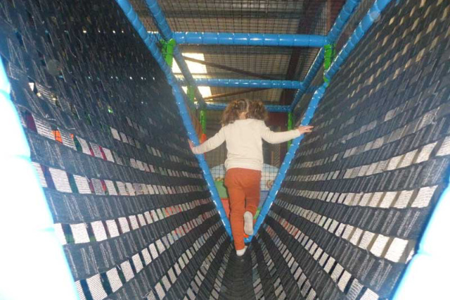 small girl walking on netting in soft play area