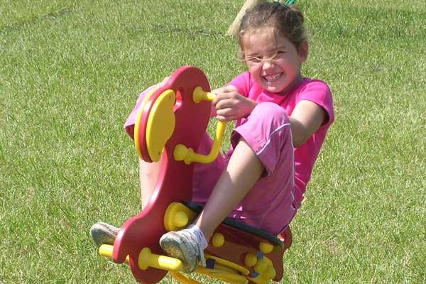 girl riding rocking horse in playground