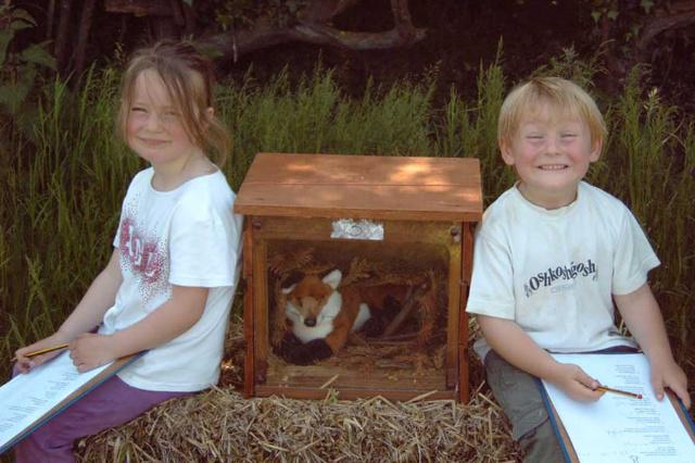 girl and boy sitting near a wildlife box